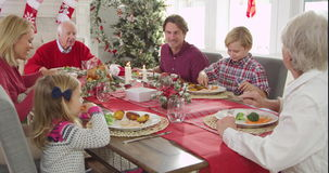 Camera tracks down to show extended family group sitting around table and enjoying Christmas meal