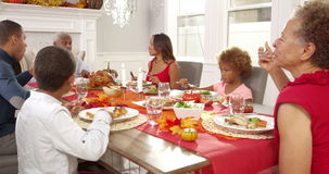 Camera tracks down to show extended family sitting around table for Thanksgiving meal stock video footage