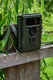 Camera trap with infrared light and motion detector attached with straps on a wooden fence Royalty Free Stock Photos