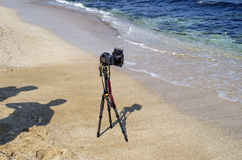 Camera on tripod at the beach and shadow of photographer Stock Image