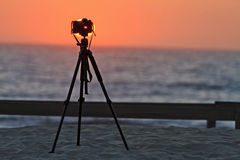 Camera on a tripod at the beach. Sunset, SLR camera Stock Images