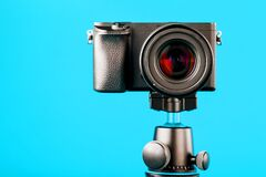 Camera on a tripod, on a blue background. Record videos and photos for your blog or report.