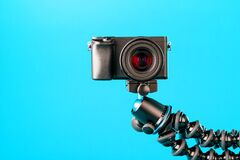 Camera on a tripod, on a blue background. Record videos and photos for your blog or report