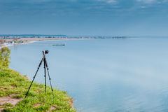 Camera with tripod on coastal cliff. Photography in severe natural and weather conditions ideas concept. Camera with tripod on coastal cliff near water Royalty Free Stock Images