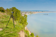 Camera with tripod on coastal cliff. Photography in severe natural and weather conditions ideas concept. Camera with tripod on coastal cliff near water Royalty Free Stock Photo