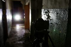 Camera on tripod in dark abandoned building. Urban exploration concept royalty free stock image