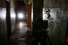 Camera on tripod in dark abandoned building. Urban exploration concept.  royalty free stock photography