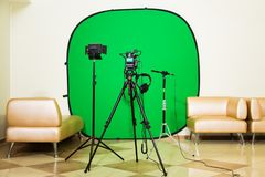 The camera on the tripod, led floodlight, headphones and a directional microphone on a green background. The chroma key Stock Image