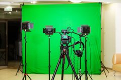The camera on the tripod, led floodlight, headphones and a directional microphone on a green background. The chroma key. Green screen Royalty Free Stock Image