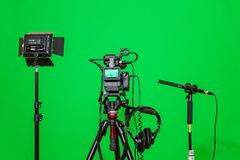 The camera on the tripod, led floodlight, headphones and a directional microphone on a green background. The chroma key Stock Images