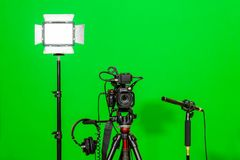 The camera on the tripod, led floodlight, headphones and a directional microphone on a green background. The chroma key Royalty Free Stock Photos
