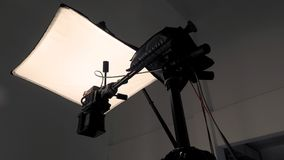 Camera and tripod with light soft box. Camera and tripod with light soft box in studio production and low angle view Stock Image