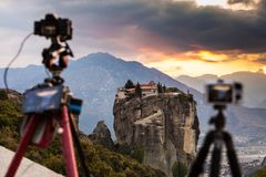 Camera on tripod and Meteora monasteries. Professional camera on tripod taking picture film video from the Holy Trinity Monastery on cliff at sunset. The Meteora Royalty Free Stock Photos
