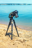 Camera on a tripod near the seaside. Removes of seashells on the sand. Photographic equipment in the process of shooting the landscape. Camera while taking a Royalty Free Stock Photography