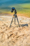 Camera on a tripod near the seaside. Removes of seashells on the sand. Photographic equipment in the process of shooting the landscape. Camera while taking a Royalty Free Stock Image
