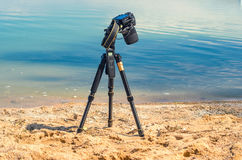 Camera on a tripod near the seaside. Removes of seashells on the sand. Photographic equipment in the process of shooting the landscape. Camera while taking a Stock Images
