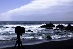 Camera on tripod with ocean and black beach in background. / El Golfo / Lanzarote / Canary Islands Royalty Free Stock Images