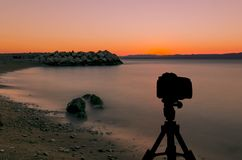 Camera on tripod with ocean and sunset in background. / Podgora, Croatia Royalty Free Stock Photography
