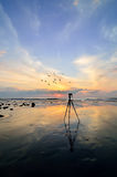 Camera with tripod over sun rising Stock Image