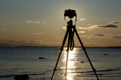 Camera with tripod over sunset near sea water. Silhouette camera with tripod over sunset near sea water Stock Images