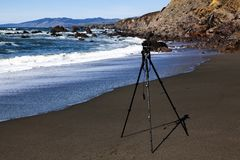 Camera On Tripod Pointing At Rocky Cliffs Sand Beach Waves royalty free stock images
