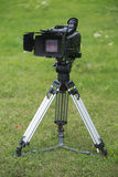 Camera on tripod. Professional tv camera on tripod stands in the green field Stock Photography