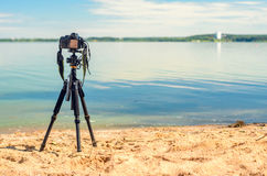 A camera on a tripod on the sandy beach. A camera on a tripod on the sandy seashore removes the seascape. Photographic equipment in the process of shooting the Royalty Free Stock Photo
