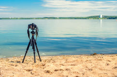 A camera on a tripod on the sandy beach. A camera on a tripod on the sandy seashore removes the seascape. Photographic equipment in the process of shooting the Stock Photos