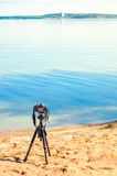 A camera on a tripod on the sandy beach. A camera on a tripod on the sandy seashore removes the seascape. Photographic equipment in the process of shooting the Stock Images