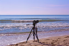 Camera on a tripod. The camera on a tripod on sea background Stock Photos
