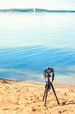 A camera on a tripod on sea background. A camera on a tripod on the sandy seashore removes the seascape. Photographic equipment in the process of shooting the Royalty Free Stock Photos