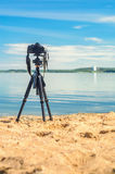 A camera on a tripod on sea background. A camera on a tripod on the sandy seashore removes the seascape. Photographic equipment in the process of shooting the Royalty Free Stock Images