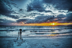 Camera on tripod by the sea. At sunset Royalty Free Stock Image