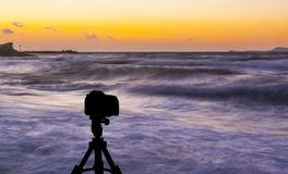 Camera on tripod with sea and sunset in background. / Gouves, Crete, Greece Royalty Free Stock Photography