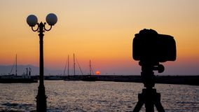 Camera on tripod with sea and sunset in background. / Gouves, Crete, Greece royalty free stock photo