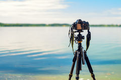 A camera on a tripod on sea background. A camera on a tripod on the seashore removes the seascape. Photographic equipment in the process of shooting the Royalty Free Stock Photo