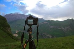 Camera on a tripod, shooting mountain scenery. Camera on a tripod, shooting mountains scenery Royalty Free Stock Images