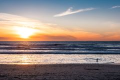 Camera with tripod shooting sunset at the beach with beautiful sunset stock images