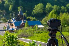 Camera on a tripod shoots a wooden Church. In the early morning Stock Photos