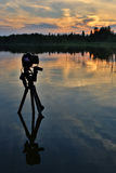 Camera on a tripod standing in the lake. Sunset on the lake. Stock Photo