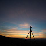 Camera on tripod in sunset Stock Photography