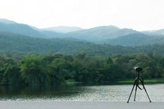 Camera with tripod take pictures of beautiful Reservoirs and mountains stock photo
