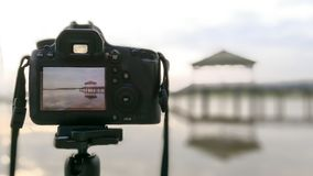 The camera is on a tripod, taking a photo of a pavilion in a pool or swamp or lake. The camera is on a tripod, taking a photo of a pavilion in a pool or swamp Stock Photos