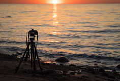 A camera on a tripod taking pictures for a timelapse on the beach. A photo camera taking pictures for a timelapse during sunset on a sandy beach in spring Stock Photography