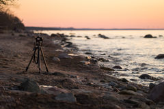 A camera on a tripod taking pictures for a timelapse on the beach. A photo camera taking pictures for a timelapse during sunset on a sandy beach in spring Stock Photos