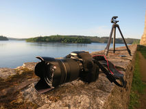 Camera with tripod on a wall. Photograph equipment next to a lake Royalty Free Stock Photography