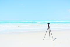Camera and tripod on white beach landscape photo Stock Photo
