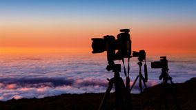 Camera tripods photographer sunset sea of clouds. Camera tripods of nature photographer work in high mountain sunset over sea of clouds Stock Image