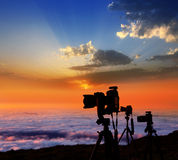 Camera tripods photographer sunset sea of clouds. Camera tripods of nature photographer work in high mountain sunset over sea of clouds Stock Photos