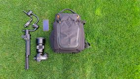 Camera and video equipment flat lay on grass. royalty free stock photo